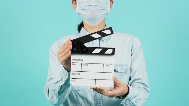 Aziatische vrouw draagt een gezichtsmasker of medisch masker en een handklep of filmleisteen op groene munt of tiffany blue achtergrond.