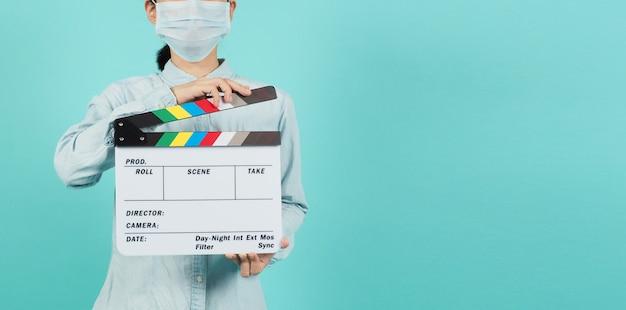 Aziatische vrouw draagt een gezichtsmasker of medisch masker en handklepelbord of filmleisteengebruik in videoproductie, bioscoopindustrie op groene munt of tiffany blue achtergrond.