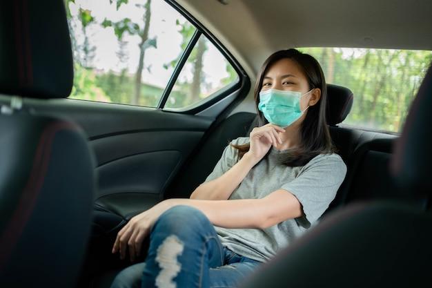 Aziatische vrouw draagt een gezichtsmasker om covid 19 in een auto te voorkomen