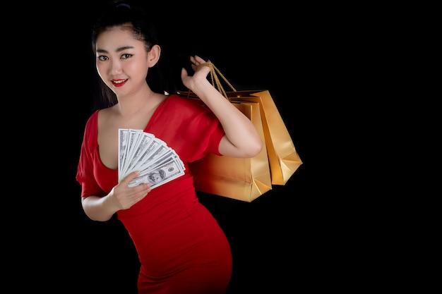 Aziatische vrouw draagt een rode jurk met een bankbiljet van 100 usd en boodschappentassen