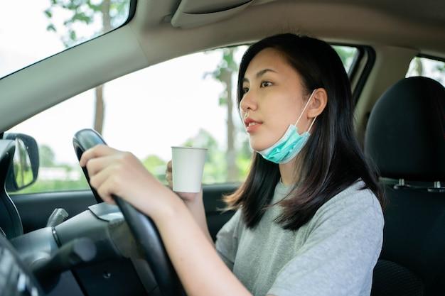 Aziatische vrouw draagt masker om covid-19 te voorkomen tijdens het rijden