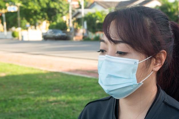 Aziatische vrouw draagt medisch masker dat beschermt tegen coronavirus of covid-19-ziekte.