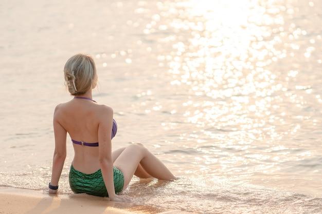 Aziatische vrouw draagt paarse en groene zeemeermin zwembroek zittend op het zandstrand.