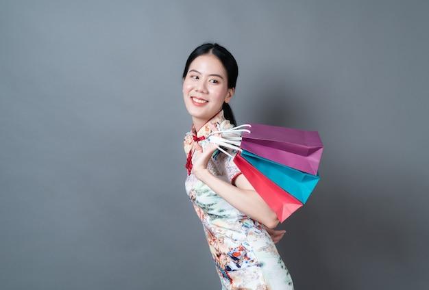 Aziatische vrouw draagt traditionele chinese kleding met boodschappentas in de hand op grijze ondergrond
