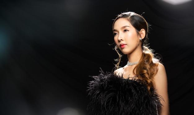 Aziatische vrouw draagt zwarte veren jurk