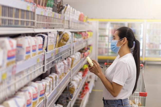 Aziatische vrouw dragen gezichtsmasker duwen winkelwagentje in supermarkt.