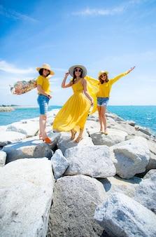 Aziatische vrouw drie die gele kleren draagt die zich op overzees strand tegen middagzonlicht bevinden