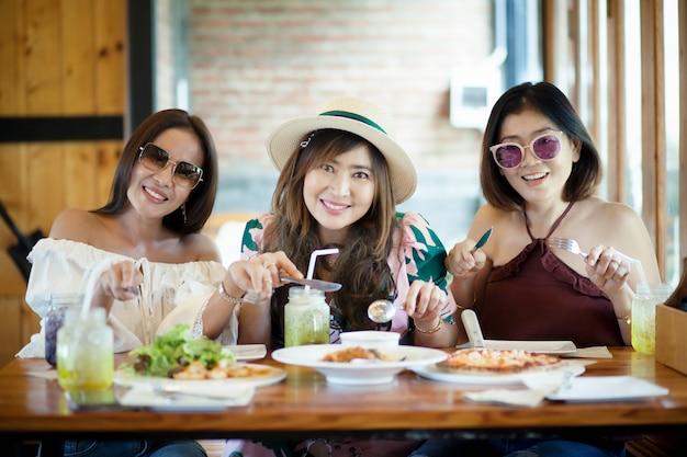 Aziatische vrouw drie klaar aan het eten van westelijk voedsel op lijst