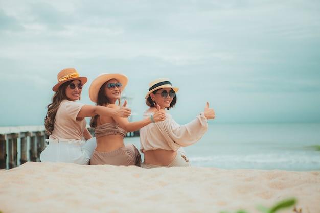 Aziatische vrouw drie zittend op vakantie zee strand met geluk emotie