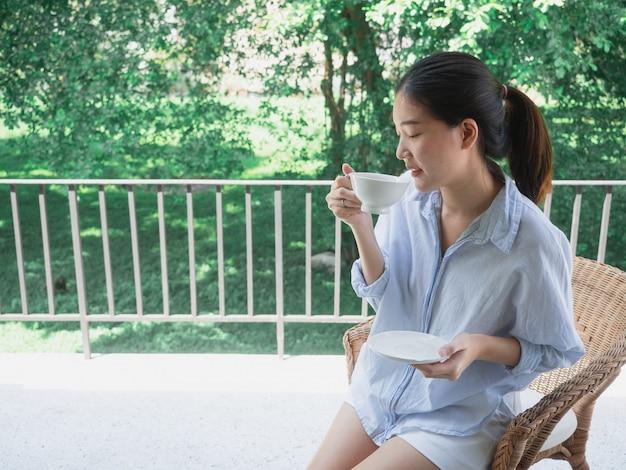 Aziatische vrouw drinkt koffie op het balkon