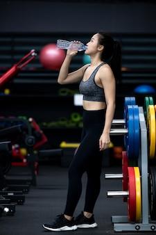 Aziatische vrouw drinkwater in de sportschool