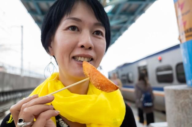 Aziatische vrouw eet taiwanese zoete frietjes in een stad
