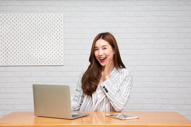 Aziatische vrouw eigenaar opstarten bedrijf met behulp van laptopcomputer en kondigen met de hand aan