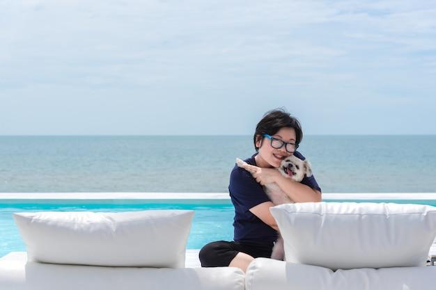Aziatische vrouw en hond die op wit strandbed bij zwembad koesteren