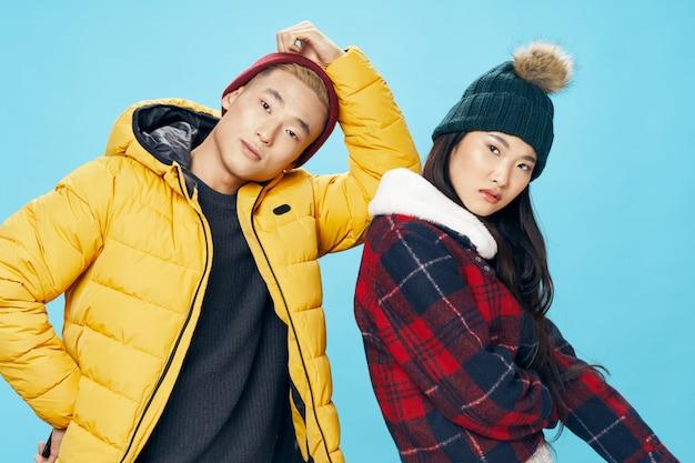Aziatische vrouw en man op het heldere stellende model van de kleurenoppervlakte samen