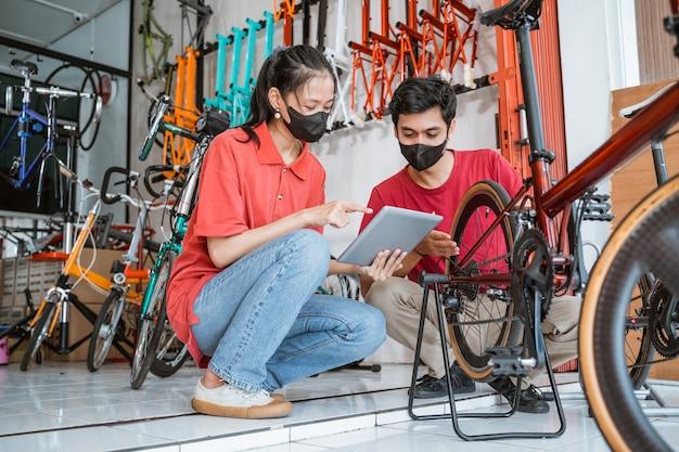 Aziatische vrouw en monteur met masker controleren een nieuwe fietsonderdelen met digitale tablet