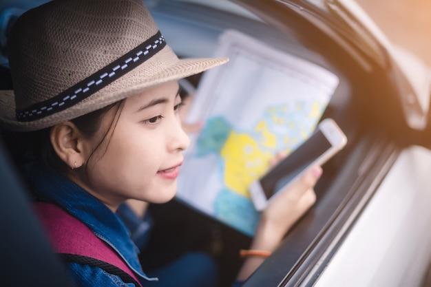 Aziatische vrouw gebruikend smartphone en kaart tussen drijfauto op wegreis