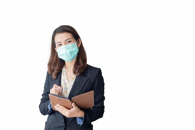 Aziatische vrouw gebruikt een tablet om thuis te werken en draagt een antivirusmasker om anderen te beschermen tegen het coronavirus