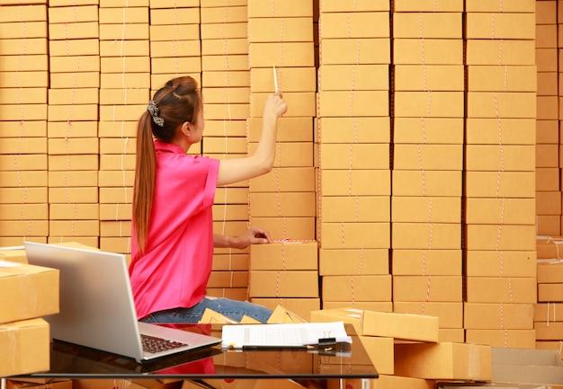 Aziatische vrouw gebruikt potlood-telpakketdozen in haar online winkelzaken thuis met laptopcomputer op bureau computer