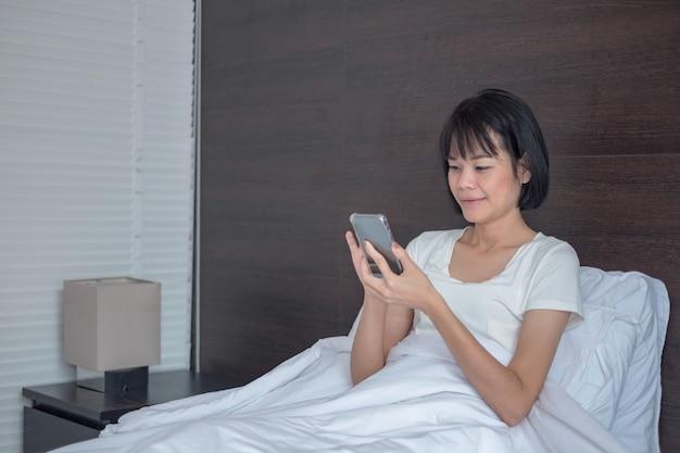 Aziatische vrouw gebruikt smartphone gelukkig op zoek naar scherm en zit thuis in het witte bed