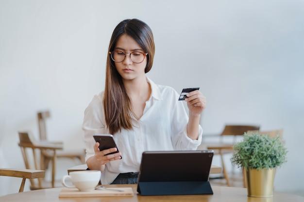 Aziatische vrouw gebruikt tablet om online te winkelen en te betalen