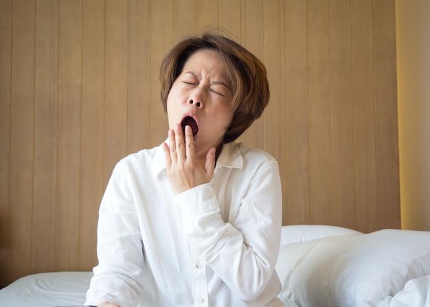 Aziatische vrouw geeuwen op bed.