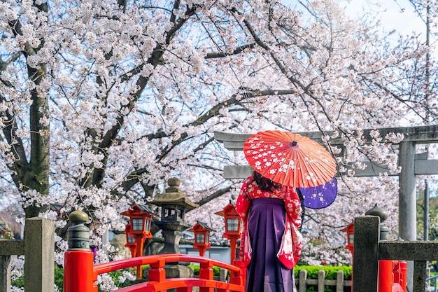 Aziatische vrouw, gekleed in japanse traditionele kimono en kersenbloesem in de lente, kyoto-tempel in japan.