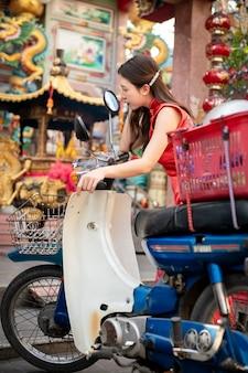 Aziatische vrouw, gekleed in rode cheongsam jurk poseren met klassieke stijl winkelen