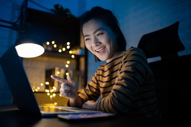 Aziatische vrouw gelukkig lachend werken op een laptop 's nachts thuis. . werk vanuit huis, vermijd het covid 19-concept.