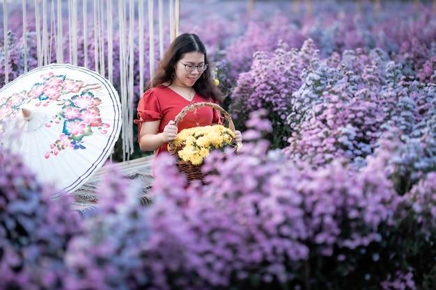 Aziatische vrouw gelukkige reiziger met rode jurk houdt witte paraplu genietend van in bloei of paars michaelmas daisy bloemenveld om een bloemenmand te houden in de natuurtuin van in chiang mai, thailand
