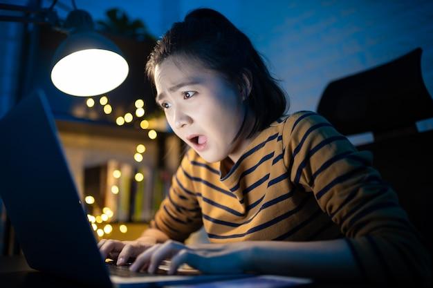 Aziatische vrouw geschokt deadline en schiet op met overuren thuis. . werk vanuit huis om het coronavirus covid 19-concept te vermijden.