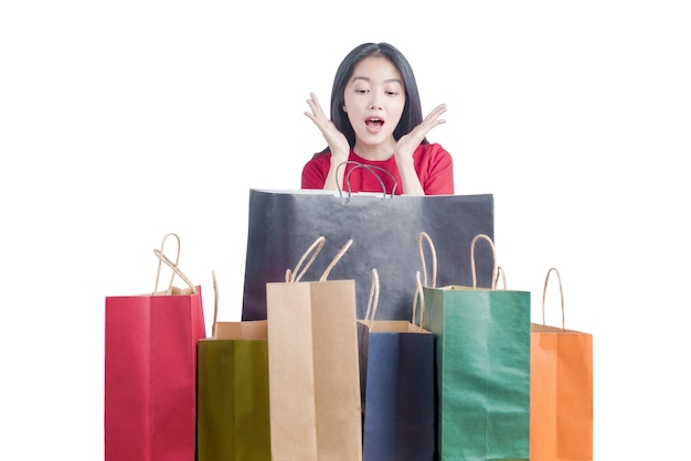 Aziatische vrouw geschokt met zo veel boodschappentassen geïsoleerd op witte achtergrond