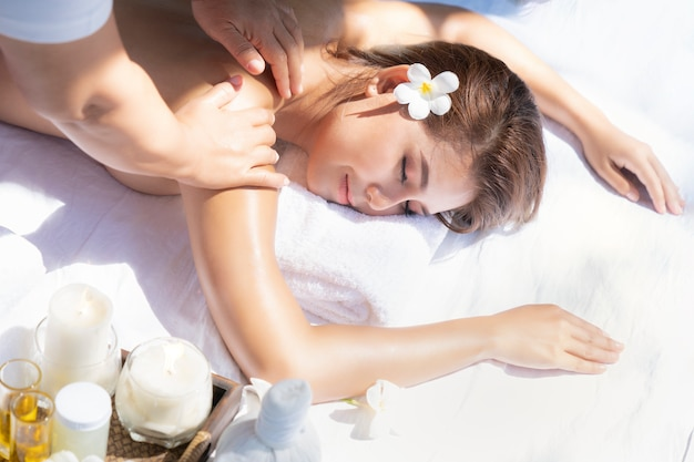 Aziatische vrouw gezicht tussen lichaamsmassage op het massagebed in spa in hotel, bangkok, thailand close-up