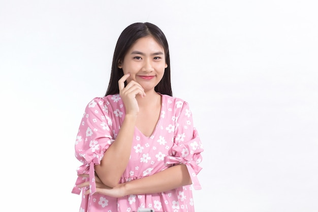 Aziatische vrouw glimlacht met een fris gezicht en draagt een roze jurk terwijl ze haar gezicht op een witte achtergrond aanraakt.