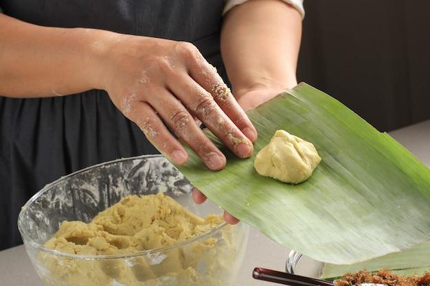 Aziatische vrouw hand maken bugis, traditionele gerechten gemaakt van kleefrijstmeel gevuld met een mengsel van suiker en geraspte kokos (unti), vervolgens verpakt in bananenbladeren en gestoomde, zoete smaak.