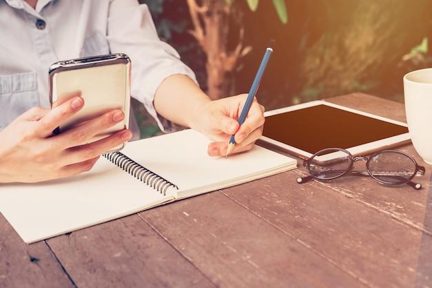 Aziatische vrouw hand met telefoon en potlood schrijven notebook in koffie winkel met vintage afgezwakt