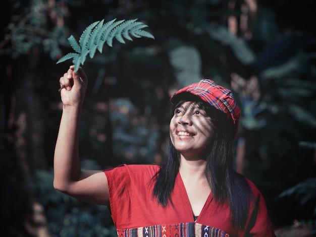 Aziatische vrouw hand met varen blad zonnescherm in het groene bos