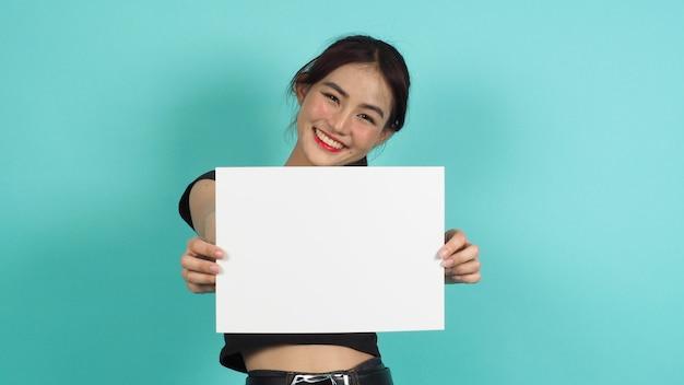 Aziatische vrouw handen houdt leeg bord met lachend gezicht op mint groene achtergrond. leeg wit a4-papier.