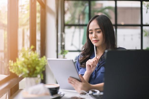 Aziatische vrouw heeft een laptop met een tablet en denkt met een glimlach in de coffeeshop.