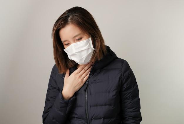 Aziatische vrouw heeft keelpijn en draagt het medische masker om infectie te beschermen en te bestrijden tegen kiemen, bacteriën, covid19, corona, sars, griepvirus. ziekte en ziekte concept