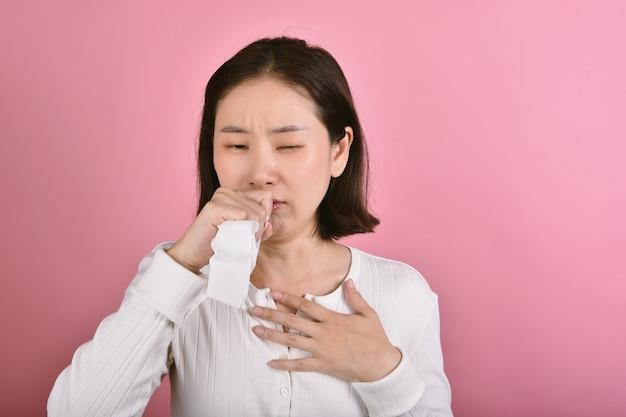 Aziatische vrouw heeft keelpijnallergie en hoesten, niezen en hoesten op openbare plaatsen zonder bescherming verspreiden druppel coronavirusziekte (covid-19)