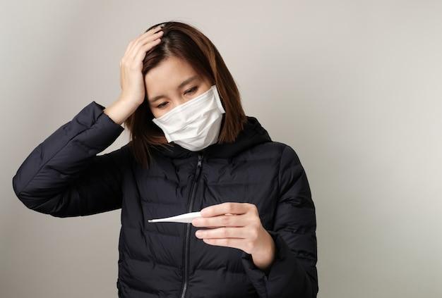 Aziatische vrouw heeft koorts en draagt het medische masker om infectie te beschermen en te bestrijden tegen kiemen, bacteriën, covid19, corona, sars, griepvirus. ziekte en ziekte concept