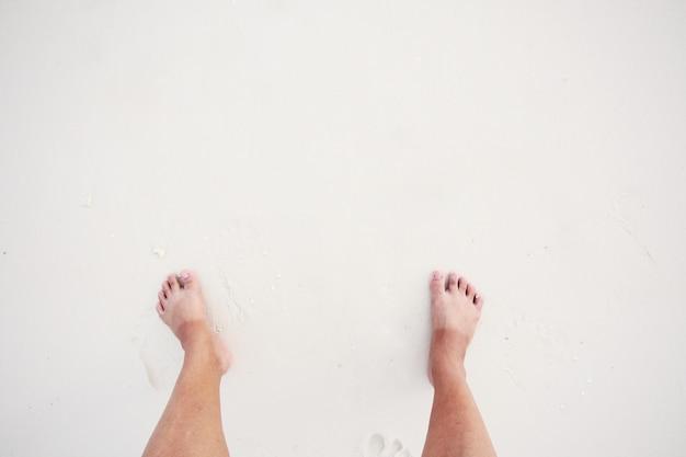 Aziatische vrouw heeft twee kleuren voet huid met zon-bad op witte strand en zee