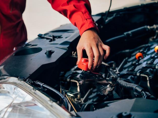 Aziatische vrouw het bevestigen van de techniek auto.