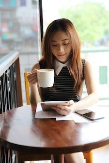 Aziatische vrouw het drinken koffie met tablet
