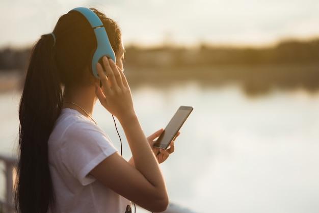 Aziatische vrouw het luisteren muziek bij het park met een vijver tijdens de avond.