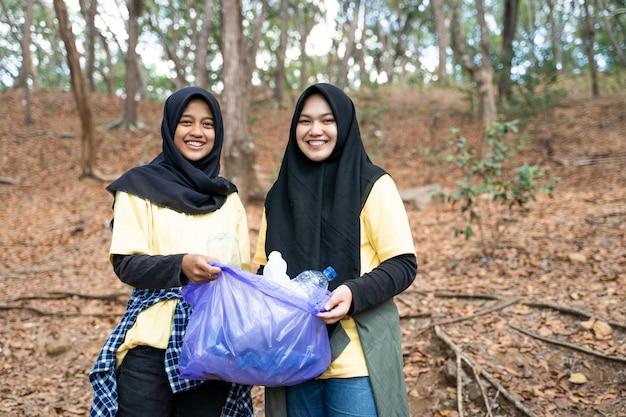 Aziatische vrouw hijab vrijwilliger vuilniszak te houden