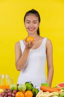 Aziatische vrouw houd sinaasappels vast met de rechterhand, en op de tafel zijn er veel vruchten.