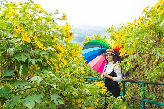 Aziatische vrouw houdt multicolor paraplu.