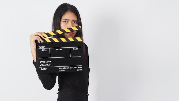 Aziatische vrouw houdt zwart klepelbord of filmlei of dakspaan vast bij videoproductie